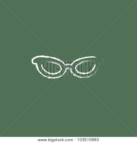 Eyeglasses hand drawn in chalk on a blackboard vector white icon isolated on a green background.