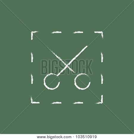 Scissors with dotted lines hand drawn in chalk on a blackboard vector white icon isolated on a green background.