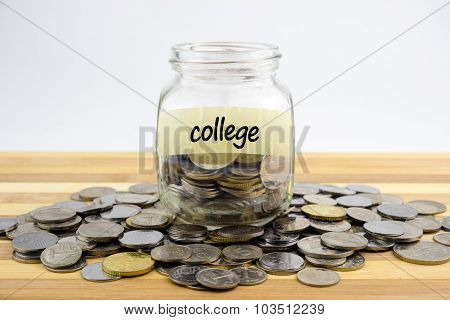 Coins In Glass Container With College Label On Wooden Surface Against White Background.financial Con
