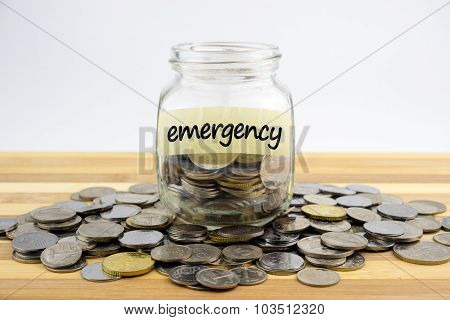 Coins In Glass Container With Emergency Label On Wooden Surface Against White Background.financial C