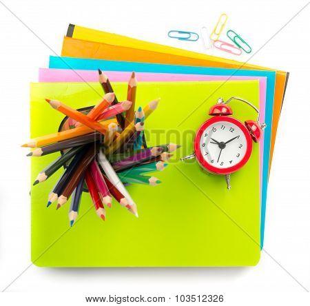 Crayons and alarm clock on copybooks