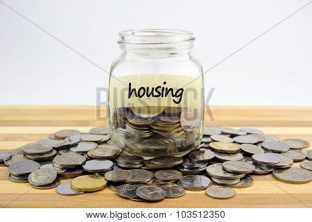 Coins In Glass Container With Housing Label On Wooden Surface Against White Background.financial Con