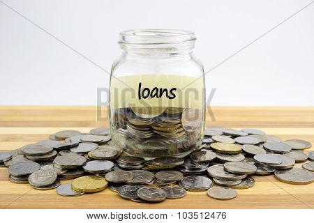 Coins In Glass Container With Loans Label On Wooden Surface Against White Background.financial Conce