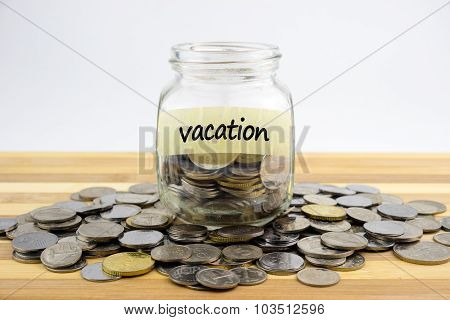 Coins In Glass Container With Vacation Label On Wooden Surface Against White Background.financial Co