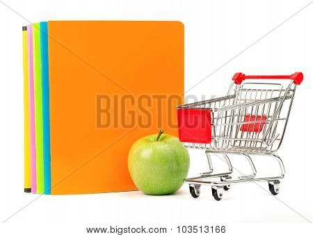 Fresh apple with exercise books and shopping cart