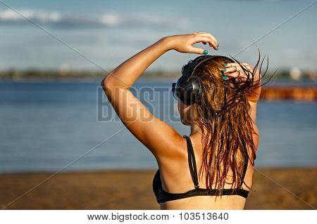 Girl Listening To Music On The Beach.