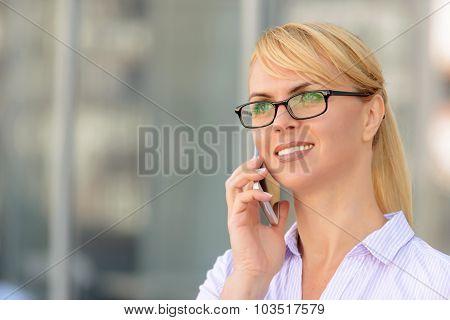Nice businesswoman standing near office building