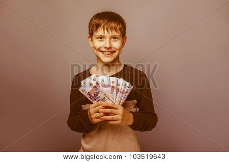 Boy teenager European appearance ten years holding a wad of mone