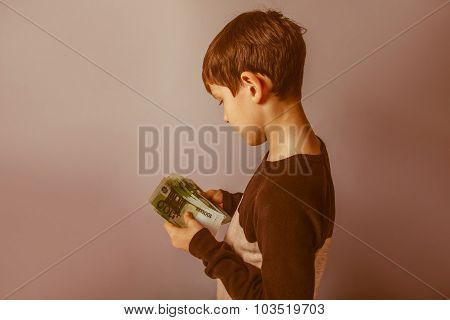 Boy teenager ten years  European appearance holding a wad  of mo