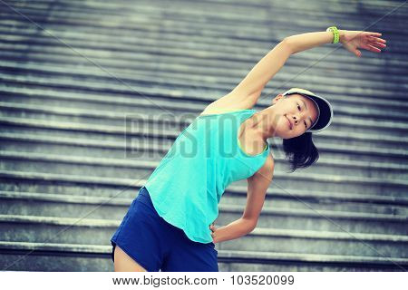 fitness woman runner stretching background city stairs