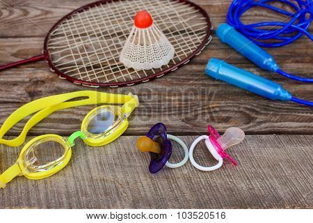 Pacifier and sports equipment: the birdie is on the racket, skipping rope, swimming goggles