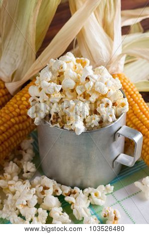 Popcorn Inside Old Cup With Several Corncobs