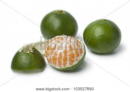 Green and peeled satsuma fruit on white background