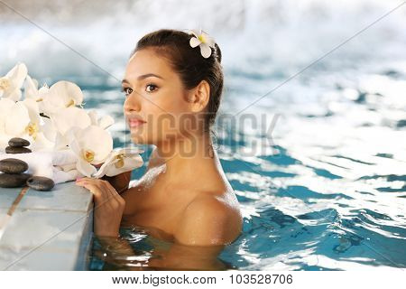 Beautiful young woman with flowers at swimming pool