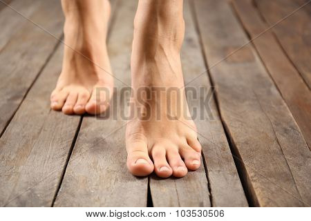 Female feet on wooden background
