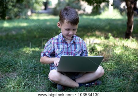 Little child is trained on the computer in the park