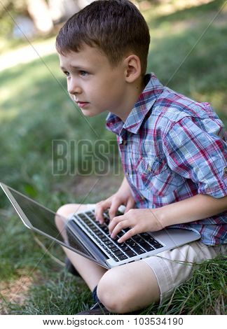 Small child thinking about the task in front of computer