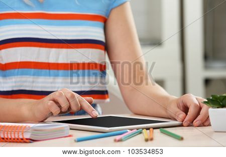 Woman using digital tablet on workplace close up
