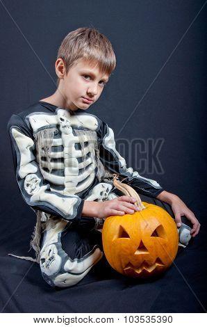 Boy In Halloween Costume With Orange Pumpkin