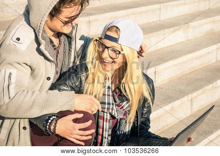 Couple Of Young Hipster People With Computer Laptop In Urban Location Outdoors