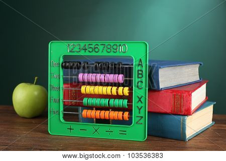 Colorful abacus with stack of book sand green apple on desk on green chalkboard background