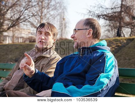 Two Older Men Talk On A Park Bench