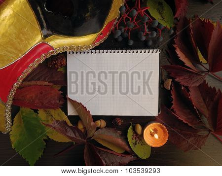 Notepad, autumn leaves, a mask with a candle on a dark surface