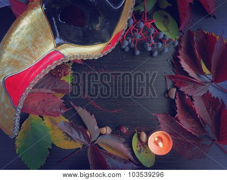 Autumn leaves and a mask with a candle on a dark surface