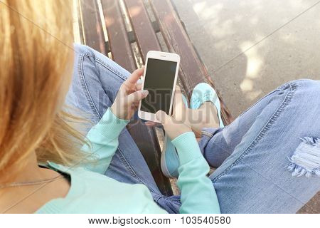 Woman with mobile phone, outdoors