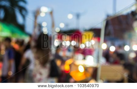 Abstract Blur Background Of People Shopping At Market Fair And The Woman Put Her Hand Up Photograph