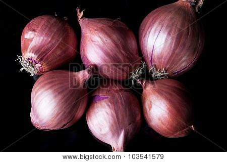 Group of shallots on black background from above