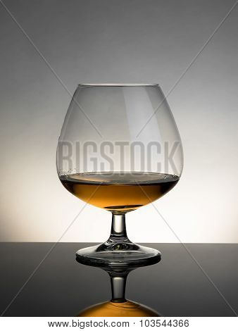 Snifter Of Brandy In Elegant Typical Cognac Glass On White Light On Grey Background