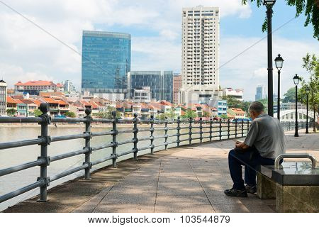 Man Sitting On A Public Bench With A View Of Urban Singapore