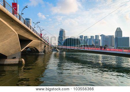 Tourists Strolling Along The New Jubilee Bridge Near Older Esplanade Bridge In Singapore.