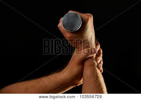 Two Male Hands With Microphone Isolated On Black