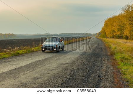 Driver of the private car saluting transport passing by on an autumnal road
