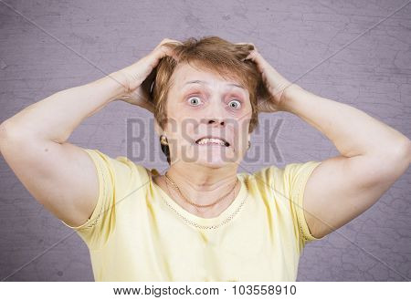 Very emotional angry woman on a gray background.