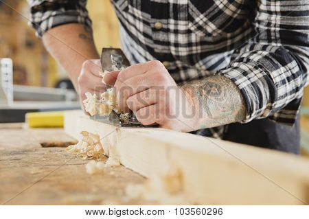 Carpenter work with plane on wood plank