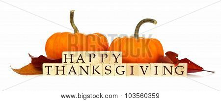 Happy Thanksgiving wooden blocks with autumn decor over white