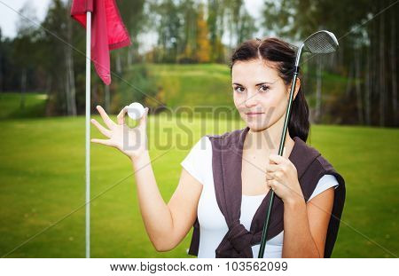 Woman Golf Player On Green With Ball And Club Near Cup