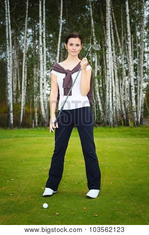 Woman Golf Player Posing On Green With Club And Ball