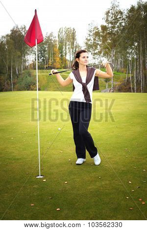 Young Woman Golf Player Posing On Green With Club