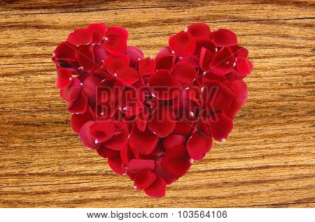 Beautiful Red Rose Petals As Heartsymbol On Wooden Background