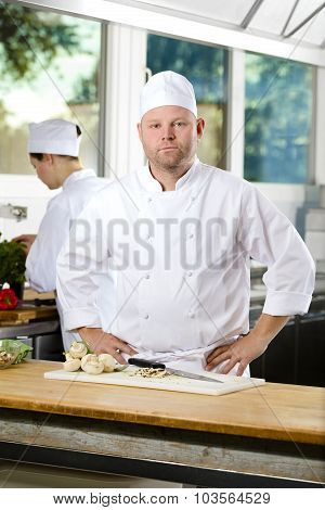 Confident chef standing in large kitchen