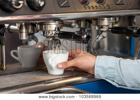 Professional male worker is making espresso in cafeteria