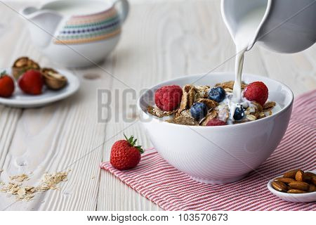 Pouring Milk Into The Bowl With Flakes