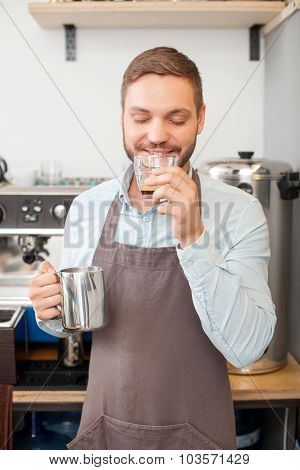 Cheerful male cafe worker is tasting made espresso
