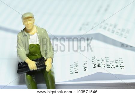 Miniature Figure Sitting On Payroll