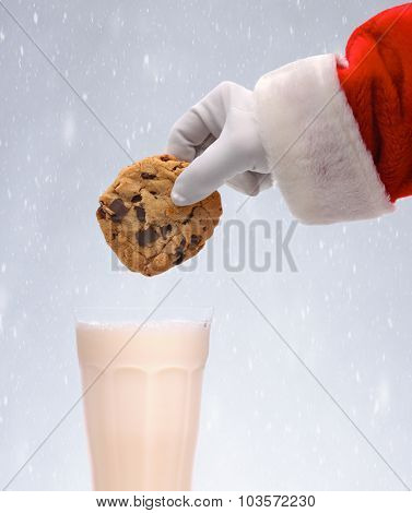 Santa Claus dunking a chocolate chip cookie into a glass of milk over a snowy background