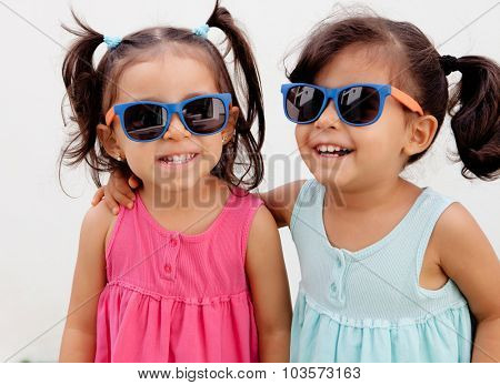 Loving twin sisters two years with sunglasses outdoors playing